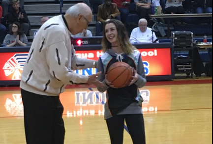 Lily Stewart is presented with the game ball for breaking the school record for most career three pointers. Recent Hall of Fame inductee, Coach Bill Kennon presented her with the game ball.